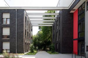 Eine offene Pergola verbindet die Wohnhäuser und wirft je nach Tagezeit ein Licht- und Schattenspiel auf die Klinkerfassade