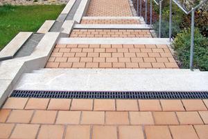 Die Einfassungen und Entwässerungs-Zeiler aus Granit-Großpflaster bilden einen dezenten Kontrast zu den Klinkern