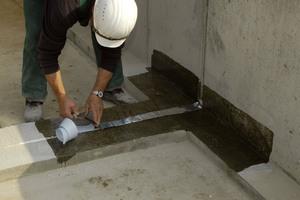 Nach der Untergrundvorbereitung bringen Handwerker Steinklebeband auf, damit bei der folgenden Abdichtung keine Zwischenhaftung entsteht