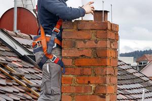 Giuseppe Trapani schiebt die neue Kunststoff-Abgasleitung in den vorhandenen Schacht. Rohr für Rohr arbeitet er sich bis ins Dachgeschoss vor