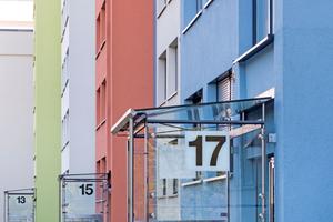 Kräftige Farbakzente in Kombination mit dunklem Grau charakterisieren die Eingänge. Ungewöhnlich ist die farbige Sockelfarbe. Die Briefkästen sind seitlich in die gläsernen Wetterschutzwände integriert. Dadurch wirkt die Eingangsfront licht und offen. Diese Wirkung wird unterstützt durch das gläserne Vordach.