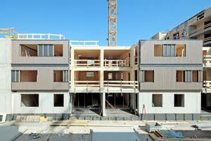 Der Holzbau ist im dreigeschossigen, hofseitigen Bauteil an der Fassade ablesbar. Die vertikale Holzverschalung transportiert die tragende Struktur an die Außenhaut