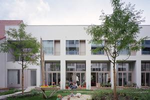 Mit der Entscheidung, großformatige Verglasungen einzusetzen, wird der gemeinschaftliche Gartenhof zum Mittelpunkt der gesamten Wohnanlage