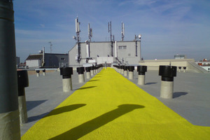 Flüssigkunststoff dichtet dauerhaft gegen eindringende Feuchtigkeit ab und weist einen rutschhemmenden Weg über ein Berliner Flachdach