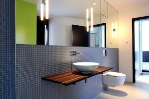 Puristische Formen und schlichte graue Mosaikfliesen prägen das Badezimmer<br />