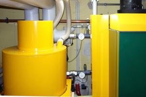 Grundlast-Pelletkessel 80 kW (rechts), Saugturbine (links) mit flexiblen Leitungen nach oben zur Außenwanddurchführung in Richtung Pelletspeicher