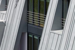 Die immer wieder anderen Fenstergeometrien und die unterschiedlichen Scharbreiten erzeugen eine bewegte Dachlandschaft