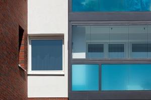 Die Balkone, ausgefacht mit punktgehaltenen VSG-Gläsern mit integrierten Farbfolien, wurden oberhalb der Brüstung mit faltbaren Wetterschutz-Verglasungen kombiniert<br />
