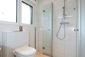 Die bodengleiche Dusche ist, wie der komplette Raum, mit rutschfesten Bodenplatten ausgestattet. Die wegklappbaren Duschwände gewähren viel Platz und Komfort
