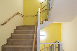 Das funktional anmutende Treppengeländer wird durch den organisch anmutenden Handlauf angenehm ergänzt. Dieser bietet Orientierung und spricht die Sinne an. In Verbindung mit dem gelben Farbton wirkt das Treppenhaus klar und einladend