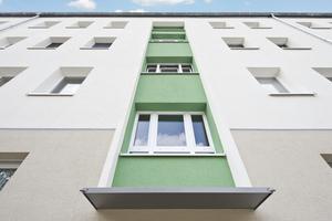 Bei diesem Mehrfamilienhaus in Köln wurde die Fassade im Bereich des Treppenhauses durch einen kräftigen Grünton akzentuiert