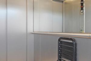 Die rollstuhlgerechte Kabine des Aufzugs ist mit Handlauf, Spiegel und Sitz ausgestattet