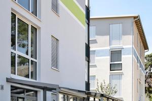 Die moderne Eingangssituation nimmt sich farblich bewusst zurück, denn akzentuiert ist die Fassade mit einer farblichen Banderole und auffälligen Balkonbrüstungen