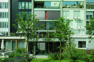 Die begrenzenden Schotten der Häuser sind aus Betonstein; jede Fassadenansicht ist durch eine eigene Architektursprache vom Nachbarn abgegrenzt