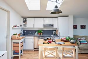 Herzstück der hellen Dachgeschosswohnung ist der zentrale Wohn-Ess-Raum mit Loftcharakter