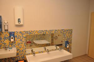 Die Warmwasserbereitung in den Sanitärräumen erfolgt effizient über Durchlauferhitzer