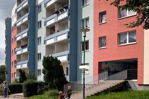 Die dunkel abgesetzten Loggien sind in der seitlichen Perspektive besonders markant. Farblich korrespondieren sie mit der Fassadenfarbe in einem hellen Blaugrau. Rote Akzentflächen bilden einen ausgleichenden Kontrast