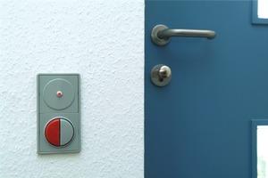 Mit dem roten Schalter an der Wohnungstür werden sämtliche Lichtquellen sowie die roten Steckdosen zentral ausgeschaltet. Die LED zeigt an, ob noch ein Fenster geöffnet ist<br />