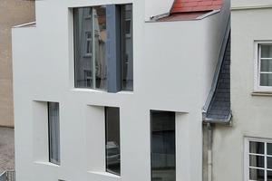 Moderne Akzente setzt das neue Wohnhaus mit den bodentiefen Fenstern, die – asymmetrisch verteilt – leicht schräg zur Fassade stehen<br />