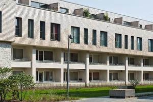 Eine hintergelüftete Fassade mit 10000 m² aus weißem Alaska Zedernholzschindeln ist die demonstrative Fortsetzung der Holzbauweise<br />